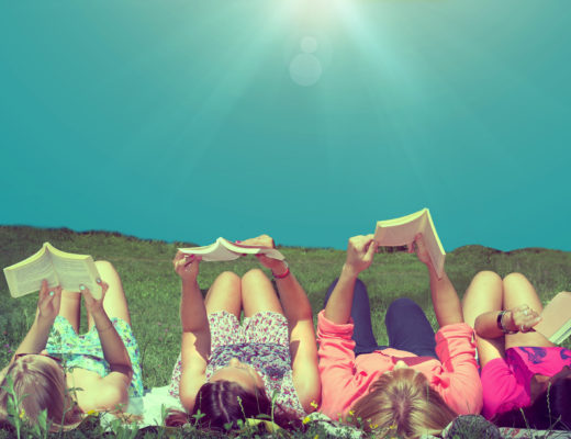 girls reading books lying on the meadow enjoying sunshine and blue sky in the summer time vintage look filtered image