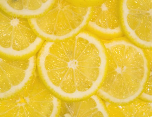 Fresh lemons background. Yellow food background. Juicy slices of lemon. Top view