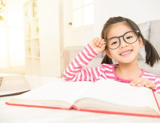 happy child little asian girl smile with holding glasses reading a books on the table in the living room at home. family activity concept.
