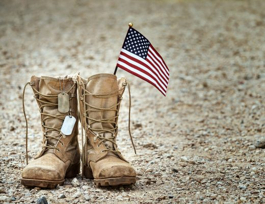 Old military combat boots with dog tags and a small American flag. Rocky gravel background with copy space. Memorial Day, Veterans day, sacrifice concept.