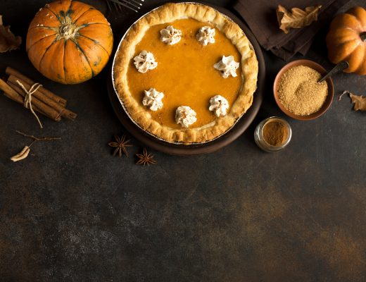 Pumpkin Pie with whipped cream and cinnamon on rustic background, top view. Homemade pastry for Thanksgiving traditional Pumpkin Pie.