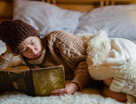 Adult woman relaxing on cozy bed in log cabin in cold winter. Reading book in warm house.