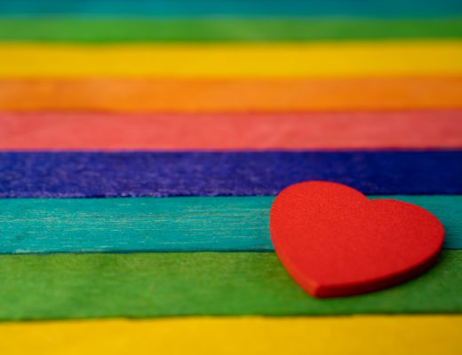 Red heart on rainbow color wooden, LGBT pride month celebrate annual in June social is a symbol of lesbian, gay, bisexual, transgender, human rights, and peace.