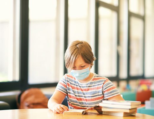 Little boy sittin in a classroom or library, wearing face mask, holding a book, back to school concept