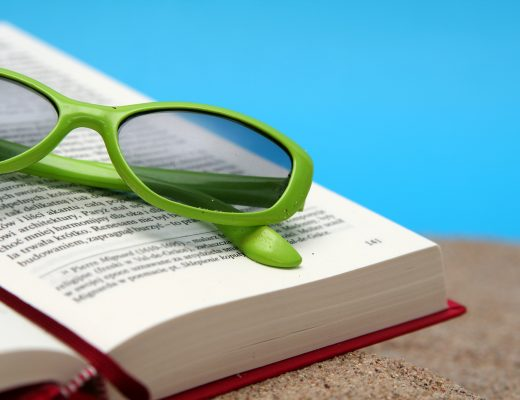 Opened book on a sand with green sunglasses